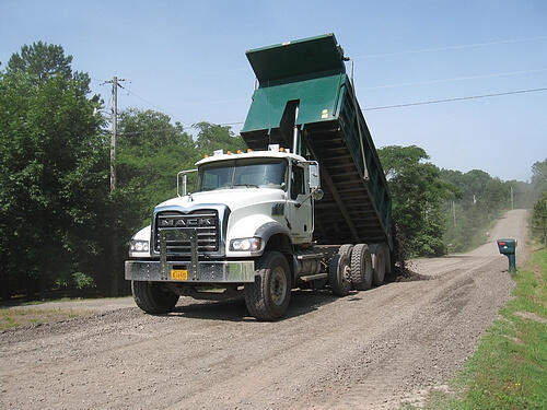 Pope County Road Department truck dumping gravel